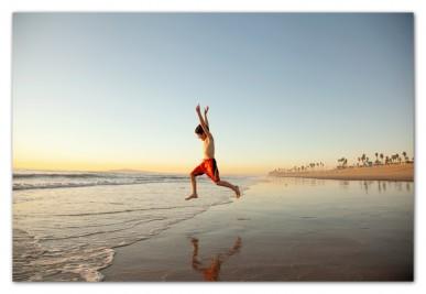 Boy running beach into ocean Huntington Beach California