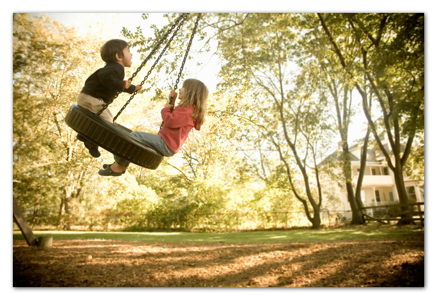 Boy and girl swinging on tire swing Wayland Massachusetts