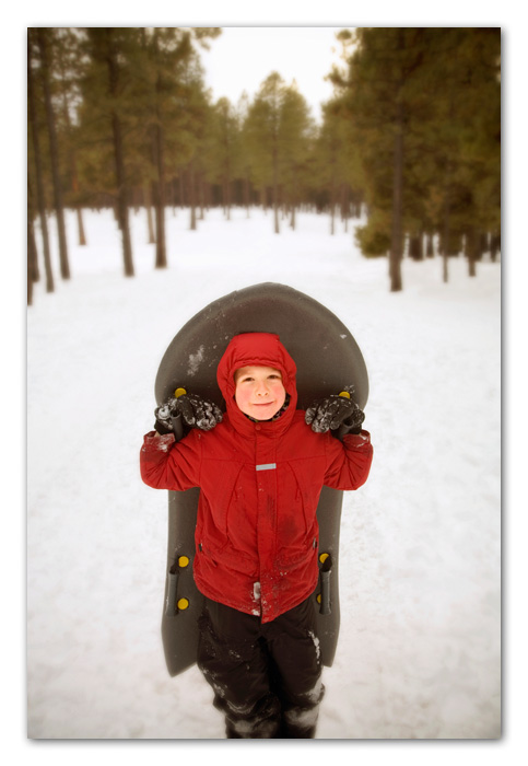 Boy with sled standing in snow Flagstaff Arizona