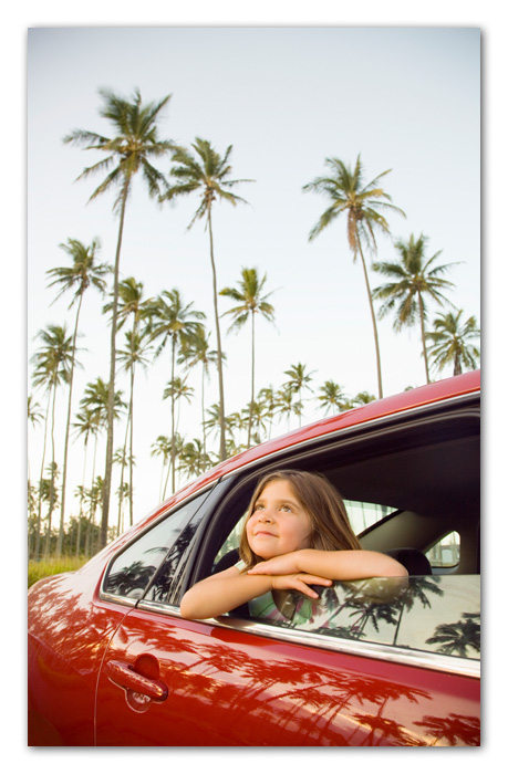 Girl looking up palm trees through car window Kapaa Kauai Hawaii