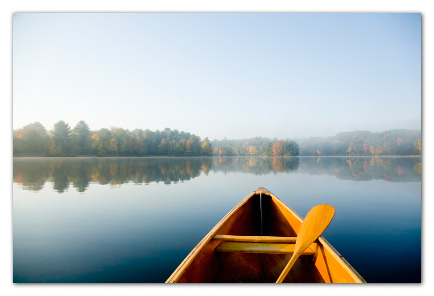 Canoe at lake in early morning in fall, Sunset Lake Massachusetts