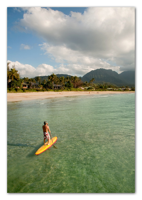 Man paddling surfboard Hanalei Bay Kauai Hawaii