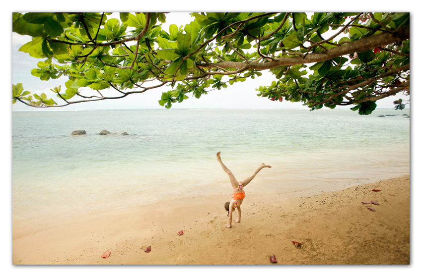 Girl doing cartwheel at beach Anini Beach Kauai Hawaii