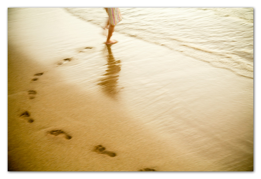Girl running on beach with footprints on sands Kapaa Kauai Hawaii